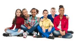Tienervrienden die op vloer het omhelzen zitten stock foto