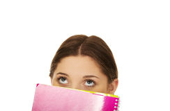 Tienervrouw het verbergen achter een notitieboekje Stock Foto's