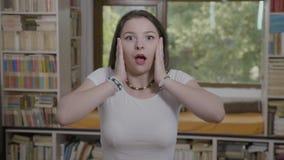 Tienervrouw ongeloof en schok met verbaasd gezicht uitdrukken en geopende mond die gezicht behandelen met handen - stock footage