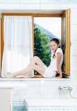 Tienerzitting op badkamersvenster royalty-vrije stock afbeeldingen