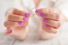 Tient des anneaux de mariage dans des mains Photographie stock libre de droits