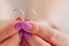 Tient des anneaux de mariage dans des mains Image stock