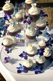 A Tier of Decorated Frosted Cupcakes. Lots of decorated chocolate and vanilla cupcakes displayed on a glass tier stand. On white table cloth, with frosting and Stock Images