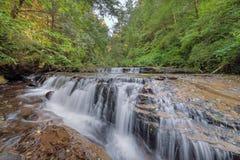 Tiered applådera vattenfall över avsatsen på den söta liten viknedgångslingan arkivfoton