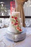 Tiered bröllopstårta tre med rosor Arkivbild