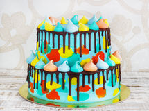 2-tiered homemade children`s cake decorated with colorful daub with meringue on white background. 2-tiered homemade children`s cake decorated with colorful daub Royalty Free Stock Photography