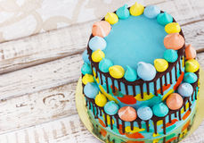 2-tiered homemade children`s cake decorated with colorful daub with meringue on white background. 2-tiered homemade children`s cake decorated with colorful daub Stock Photos