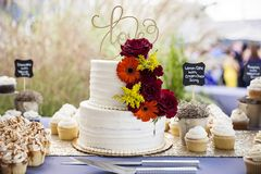 Wedding cake on table at garden wedding. A tiered wedding cake with autumn colored flowers, red, orange and yellow and gold love topper sitting on a table at an royalty free stock image