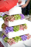 Tiered wedding cake with flower. Closeup of tiered white wedding cake decorated with real flowers Royalty Free Stock Photos
