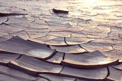 Tierra agrietada en la luz de la puesta del sol Fotografía de archivo