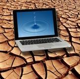 Tierra agrietada seca y agua pura en la pantalla de la computadora portátil fotos de archivo