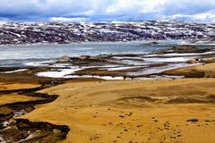 Tierra de Brown, lago gris, montañas blancos y negros, cielo azul Imagen de archivo