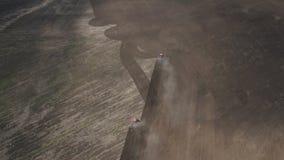 Tierra de cultivaci?n de los tractores Vista a?rea de los campos de la cosecha con los tractores Maquinaria agr?cola en el arado  metrajes