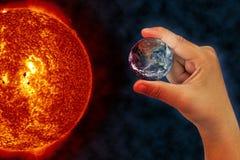 Tierra del planeta en la mano con la quemadura del sol Imagen de archivo libre de regalías