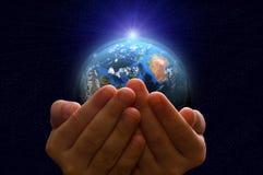 Tierra del planeta en las manos de un niño fotos de archivo