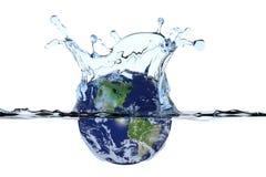 Tierra del planeta que salpica en agua Foto de archivo