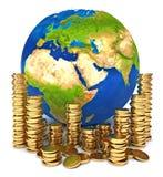 Tierra del planeta y una pila de monedas de oro Imagenes de archivo