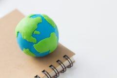 Tierra en el cuaderno en el fondo blanco Imagen de archivo