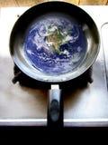 Tierra en el sartén que muestra el calentamiento del planeta Fotografía de archivo libre de regalías