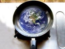 Tierra en el sartén que muestra el calentamiento del planeta Foto de archivo