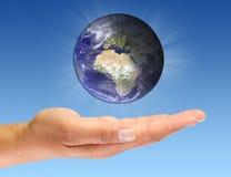Tierra que brilla intensamente en la palma abierta Foto de archivo