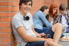 Tierra que se sienta del muchacho del estudiante universitario con los amigos Imagen de archivo libre de regalías