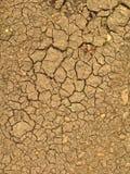 Tierra seca en grietas grandes después de una sequía del color marrón Foto de archivo