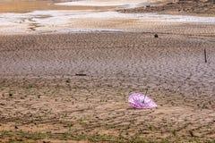 Tierra seca y agrietada sin lluvia y un paraguas quebrado fotografía de archivo
