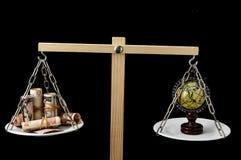 Tierra y dinero en dos Pan Balance Imagenes de archivo