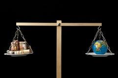 Tierra y dinero en dos Pan Balance Foto de archivo