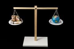 Tierra y dinero en dos Pan Balance Fotos de archivo libres de regalías