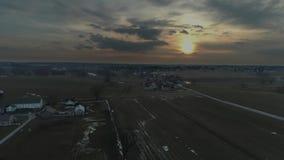 Tierras de cultivo de Amish en la puesta del sol en un d?a de invierno tempestuoso seg?n lo visto por un abej?n almacen de metraje de vídeo