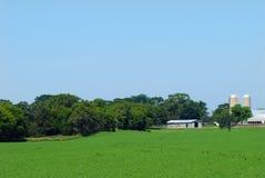Tierras de labrantío con los graneros y los silos Foto de archivo libre de regalías