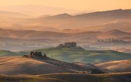 Tierras de labrantío de Toscana con los chalets y los pueblos Fotos de archivo