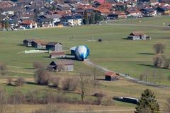 Tierras del globo del aire caliente en un prado Fotografía de archivo libre de regalías