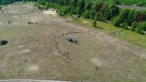 Tierras del helicóptero en un campo El helicóptero en el medio del campo verde se prepara para volar El helicóptero llegó en camp Fotos de archivo libres de regalías