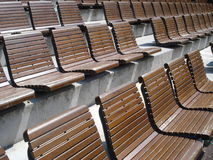 Tiers of wooden chairs in outdoor arena. Tiers of wooden armless fixed chairs in outdoor sports arena Royalty Free Stock Photography