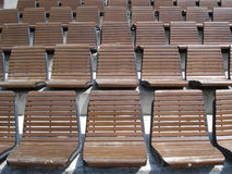 Tiers of wooden chairs in outdoor arena. Tiers of wooden armless fixed chairs in outdoor sports arena Stock Image