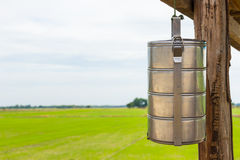 The tiffin carrier on green field background Stock Photography