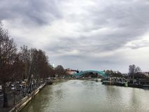 TIFLIS, GEORGIA - 11. MÄRZ 2016: Die Brücke dehnt über die Kura aus und schließt die Bereiche von altem Tiflis an Lizenzfreie Stockfotografie