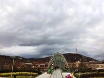 TIFLIS, GEORGIA - 11. MÄRZ 2016: Die Brücke dehnt über die Kura aus und schließt die Bereiche von altem Tiflis an Stockbild