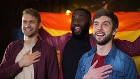 Tifosi maschii multietnici spagnoli che cantano inno nazionale e che ondeggiano bandiera stock footage
