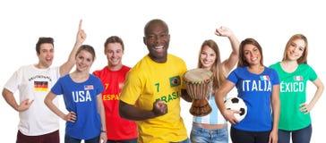 Tifoso brasiliano incoraggiante con il tamburo ed altri fan fotografia stock