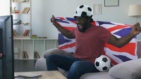 Tifoso britannico eccitato dal gioco, incoraggiante per il gruppo con la bandiera nazionale archivi video