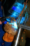 TIG Welding. The TIG welder's protective helmet and leather glove are illuminated by the  arc and the sparks Royalty Free Stock Photo