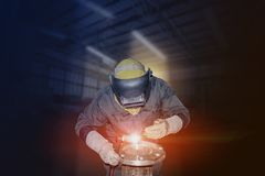 Tig welding industries. Worker man Tig gas argon welding metal pipe isolated on dark tone background Royalty Free Stock Photo
