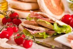 Tigella bröd som är välfyllt med skinka och grönsallat Royaltyfri Fotografi