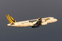 Tiger Airways Airbus A320-232 VH-VNK departing Melbourne International Airport with dark storm clouds behind. stock photos