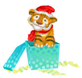 A tiger cub sits near boxes with gifts. Tiger cub in a little cap and scarf  as symbol of 2010 Royalty Free Stock Photo
