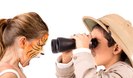 Tiger and explorer. Beautiful young girl with face painted like a tiger and boy explorer with binoculars Stock Photography